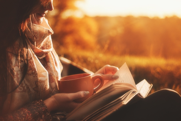 Beautiful girl in autumn forest reading a book covered with a warm blanket.a woman sits near a tree in an autumn forest and holds a book and. Girl reading a book