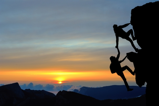 The joint work teamwork of two men travelers help each other on top of a mountain climbing team a beautiful sunset landscape