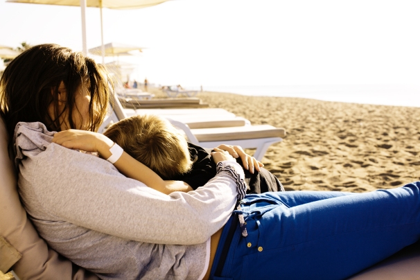 young mother with son resting on sea coast happy family together talking lifestyle people concept.jpg